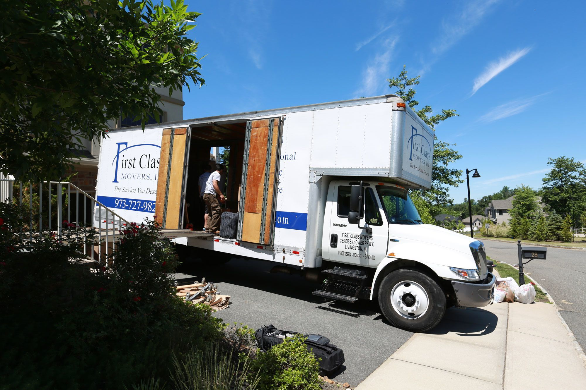 moving-truck-in-front-of-house-professional-movers-inside-truck